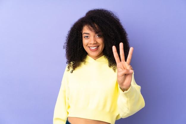幸せな紫と指で3つを数えるに分離された若いアフリカ系アメリカ人女性