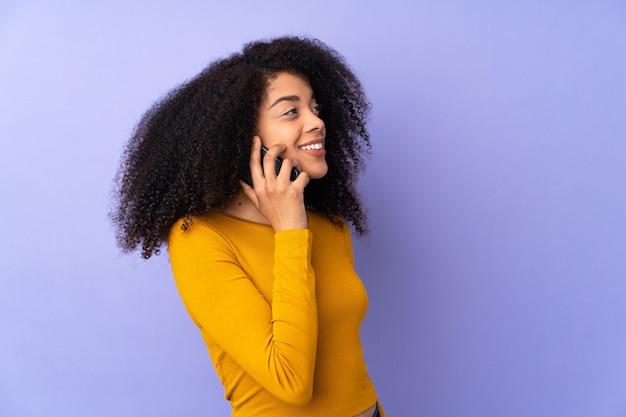 Молодая афро-американская женщина изолирована на фиолетовом и разговаривает с кем-то по мобильному телефону