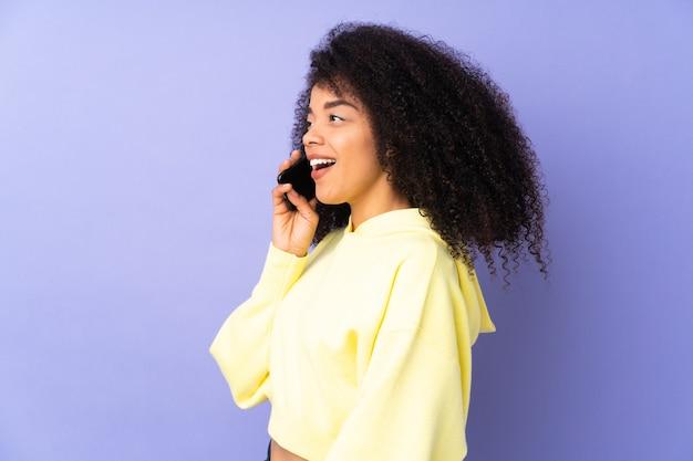 Молодая афро-американская женщина изолирована на фиолетовом и разговаривает по мобильному телефону