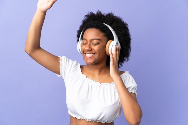 Молодая афро-американская женщина изолирована на фиолетовом, слушает музыку и танцует