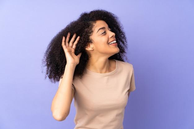 Молодая афро-американская женщина изолирована на фиолетовом, слушая что-то, положив руку на ухо