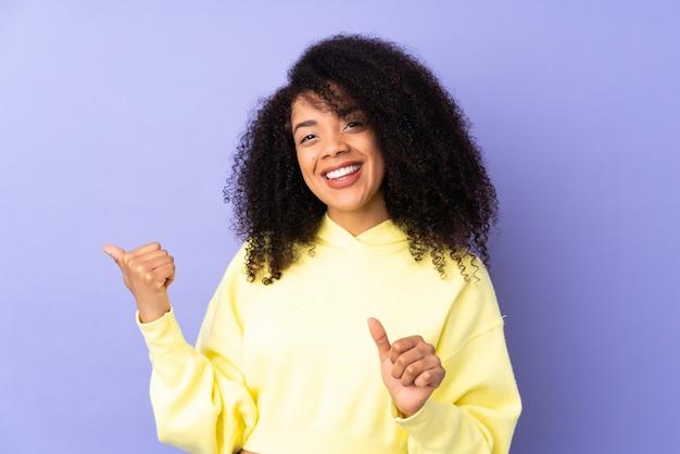 製品を提示する側を指している紫に分離された若いアフリカ系アメリカ人女性