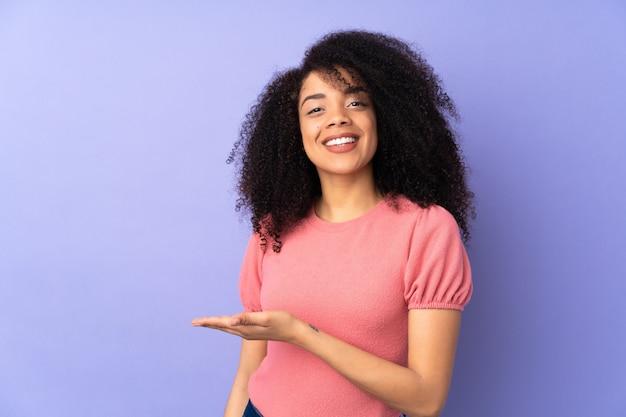 に向かって笑みを浮かべながら見ているアイデアを提示する紫に分離された若いアフリカ系アメリカ人女性