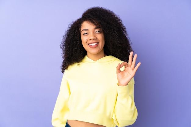 指でokの標識を示す紫に分離された若いアフリカ系アメリカ人女性