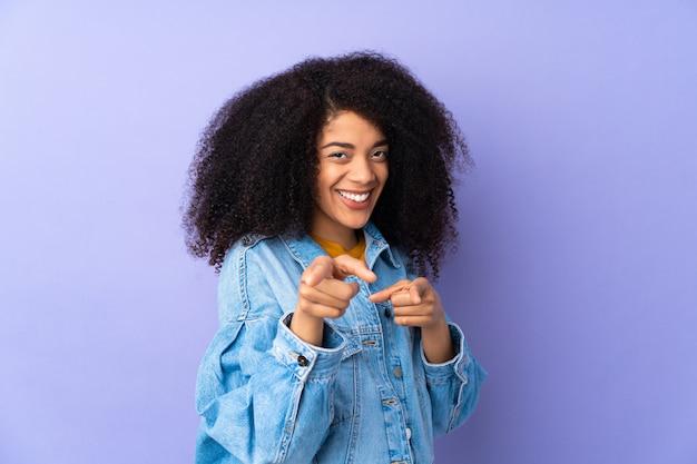 紫の驚きと指差し前に分離された若いアフリカ系アメリカ人女性