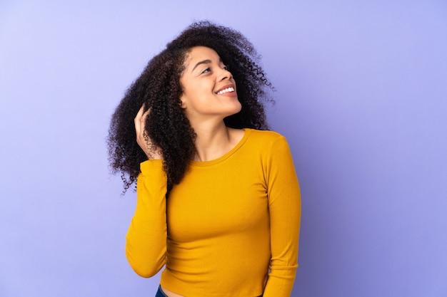 アイデアを考えて紫に分離された若いアフリカ系アメリカ人女性