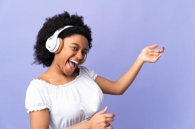 음악을 듣고 기타 제스처를 하 고 보라색 벽에 고립 된 젊은 아프리카 계 미국인 여자