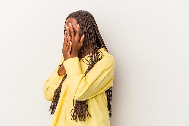 白い背景で隔離の若いアフリカ系アメリカ人の女性は、おびえ、神経質な指を点滅します。