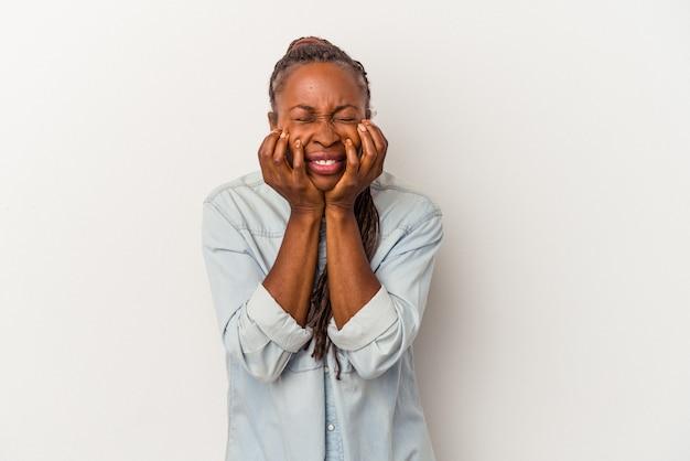 Молодая афро-американская женщина, изолированных на белом фоне, плачет, недовольна чем-то, агонией и концепцией замешательства.