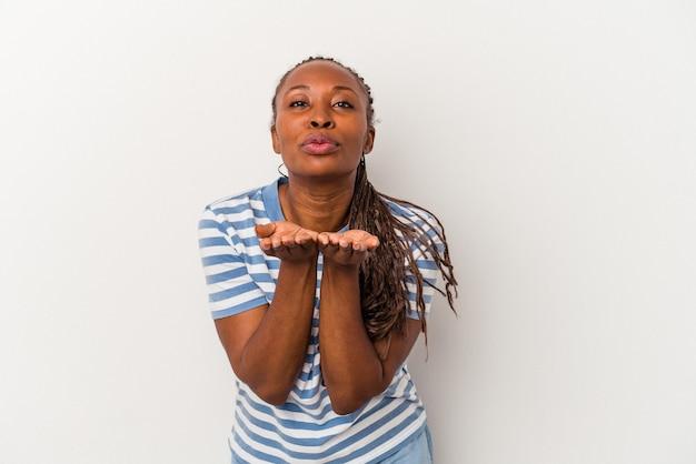 唇を折り、手のひらを持って空気のキスを送信する白い背景で隔離の若いアフリカ系アメリカ人女性。