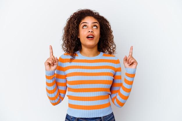 열린 된 입으로 거꾸로 가리키는 흰색 배경에 고립 된 젊은 아프리카 계 미국인 여자.