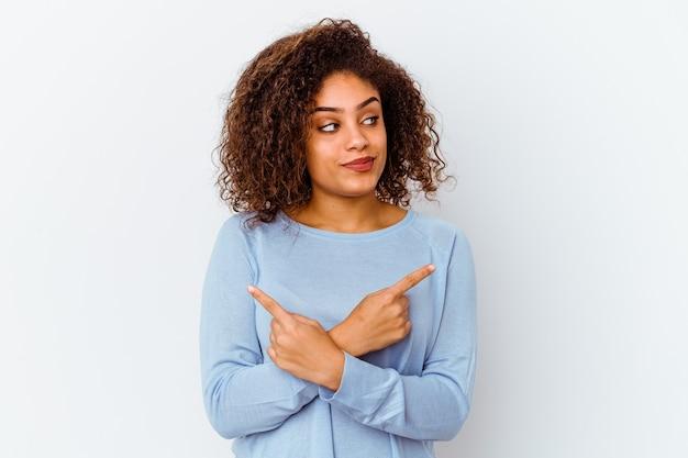 흰색 배경 포인트 옆에 고립 된 젊은 아프리카 계 미국인 여자는 두 가지 옵션 사이에서 선택하려고합니다.