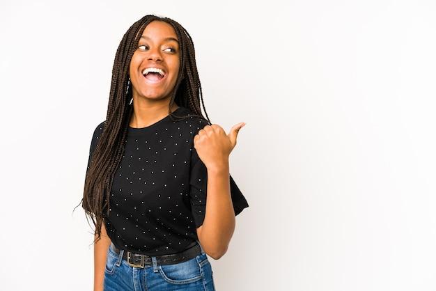 Молодая афро-американская женщина, изолированная на белом фоне, указывает пальцем далеко, смеясь и беззаботно.