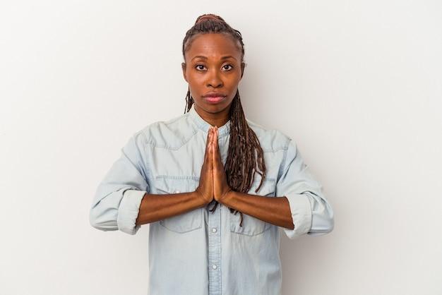 Молодая афро-американская женщина, изолированные на белом фоне, молясь, показывая преданность, религиозный человек, ищущий божественного вдохновения.