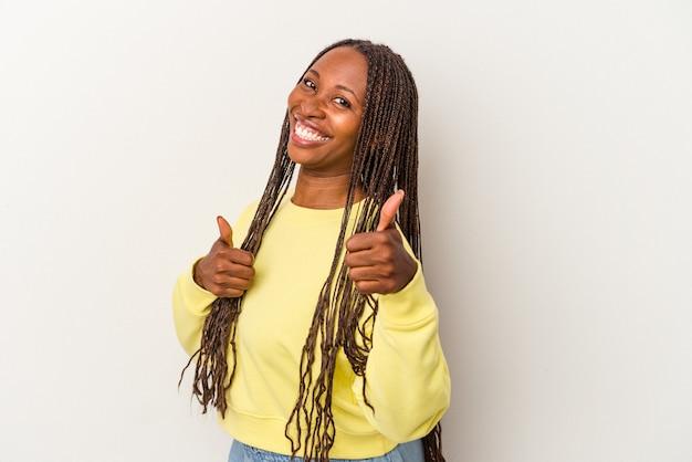 若いアフリカ系アメリカ人の女性は、白い背景に孤立し、両方の親指を上げて、笑顔で自信を持っています。