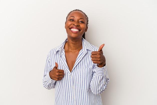 若いアフリカ系アメリカ人の女性は、白い背景で隔離され、両方の親指を上げて、笑顔で自信を持っています。