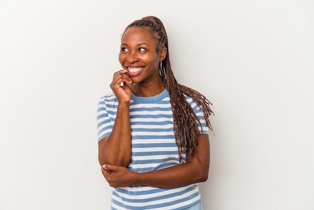 Молодая афро-американская женщина, изолированных на белом фоне, расслабилась, думая о чем-то, глядя на копию пространства.