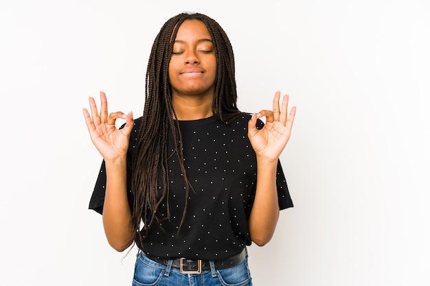 흰색 배경에 고립 된 젊은 아프리카 계 미국인 여자는 열심히 일한 후 이완, 그녀는 요가 수행합니다.