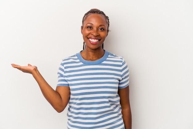 Молодая афро-американская женщина, изолированные на белом фоне, показывая пространство для копии на ладони и держа другую руку на талии.