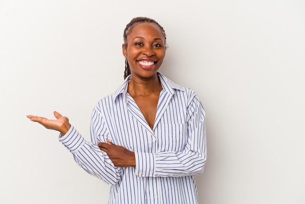手のひらにコピースペースを示し、腰に別の手を保持している白い背景で隔離の若いアフリカ系アメリカ人女性。