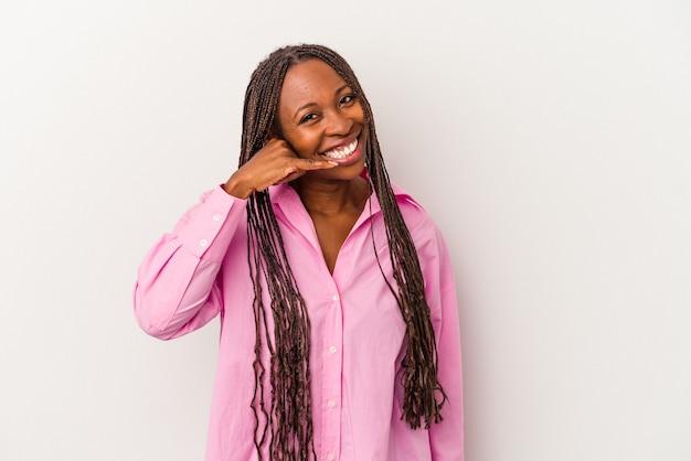 指で携帯電話の呼び出しジェスチャーを示す白い背景で隔離の若いアフリカ系アメリカ人女性。