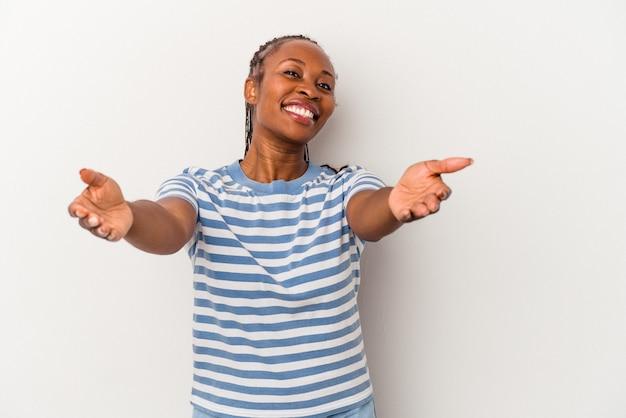 歓迎の表現を示す白い背景で隔離の若いアフリカ系アメリカ人女性。
