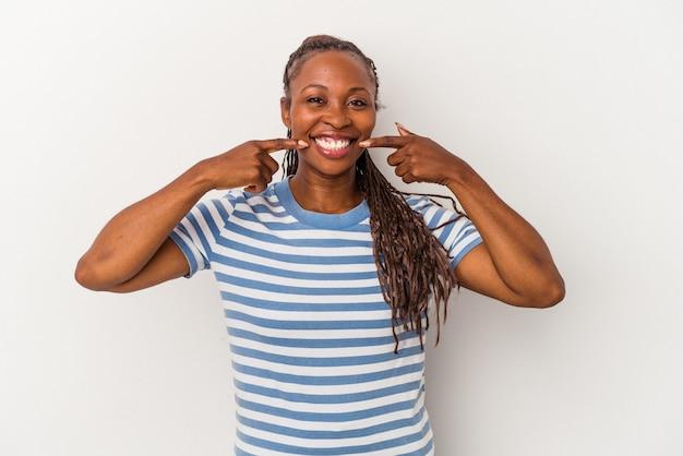Молодая афро-американская женщина, изолированные на белом фоне улыбается, указывая пальцами на рот.