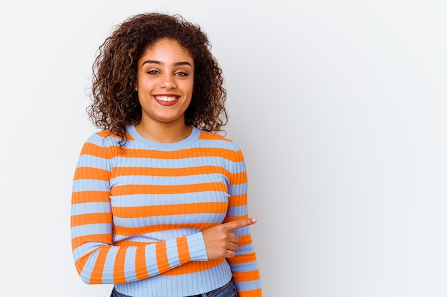 웃 고 제쳐두고, 빈 공간에서 뭔가 보여주는 흰색 배경에 고립 된 젊은 아프리카 계 미국인 여자.