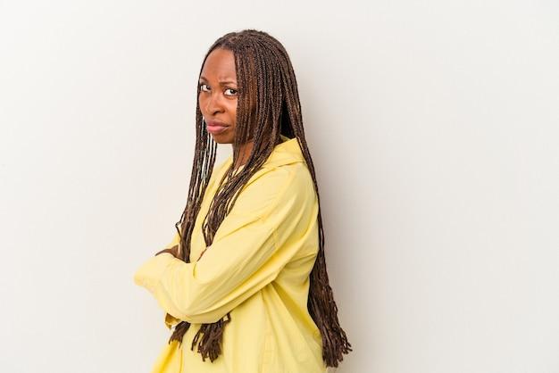 Молодая афро-американская женщина, изолированные на белом фоне, подозрительно, неуверенно, изучает вас.