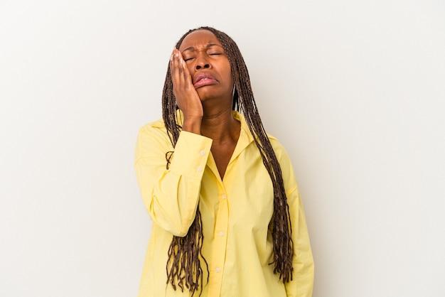 白い背景に孤立した若いアフリカ系アメリカ人の女性は疲れていて、頭に手を置いて非常に眠いです。