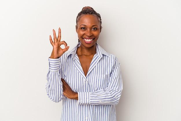 Молодая афро-американская женщина, изолированная на белом фоне, подмигивает и держит рукой жест хорошо.