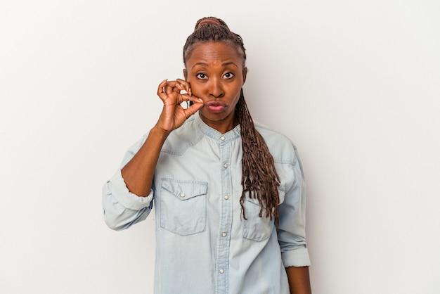 Молодая афро-американская женщина, изолированные на белом фоне с пальцами на губах, сохраняя в секрете.