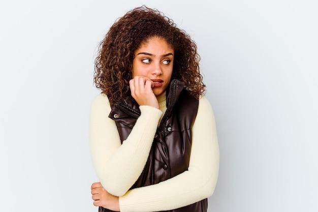 指の爪を噛む白い壁に孤立した若いアフリカ系アメリカ人女性、神経質で非常に不安