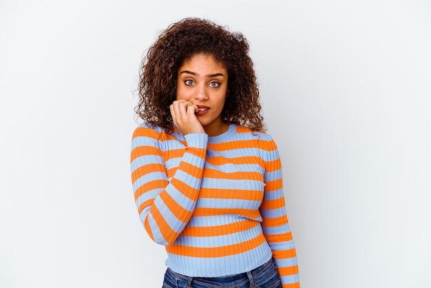 Молодая афро-американская женщина, изолированная на белой стене, кусая ногти, нервничает и очень тревожится.