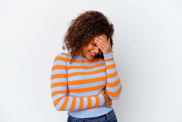 白い壁に隔離された若いアフリカ系アメリカ人の女性が指で正面を点滅し、恥ずかしい顔を覆っている