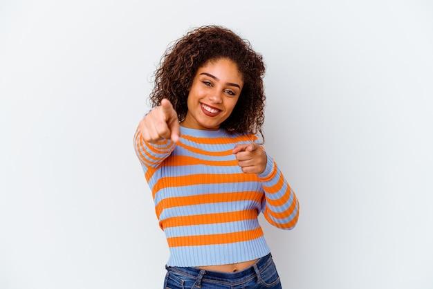 Молодая афро-американская женщина изолированная на белой стене веселые улыбки указывая к фронту.