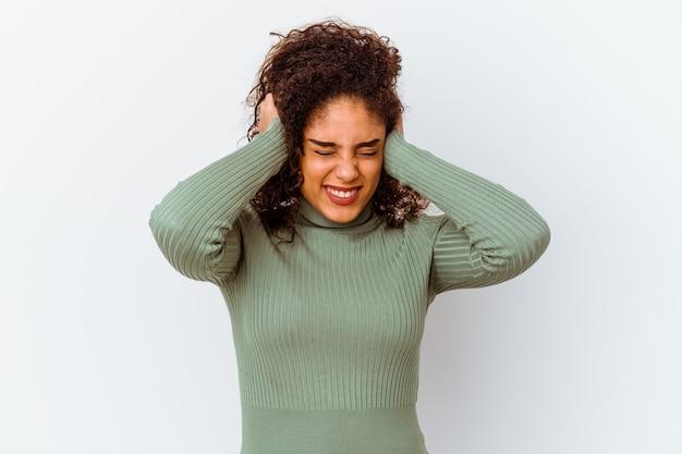 手で耳を覆う白い壁に分離された若いアフリカ系アメリカ人女性。