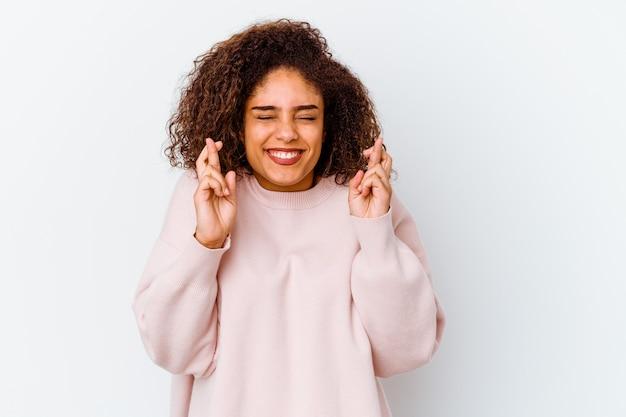 행운을 갖는 흰 벽 횡단 손가락에 고립 된 젊은 아프리카 계 미국인 여자