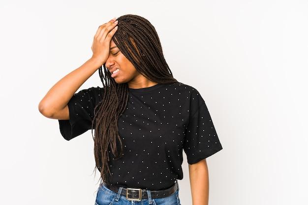 뭔가 잊고, 손바닥으로 이마를 때리고 눈을 감고 흰 벽에 고립 된 젊은 아프리카 계 미국인 여자.