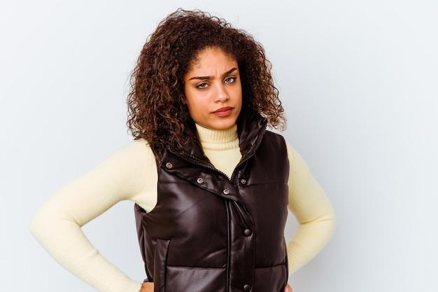 不快な顔をしかめている白い壁に孤立した若いアフリカ系アメリカ人の女性は、腕を組んでいます。