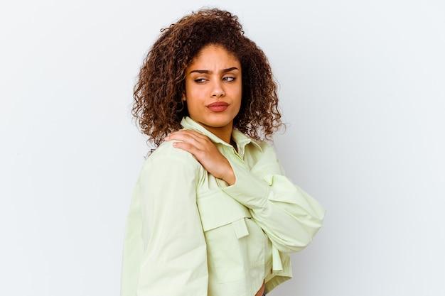肩の痛みを抱えている白い壁に孤立した若いアフリカ系アメリカ人女性。