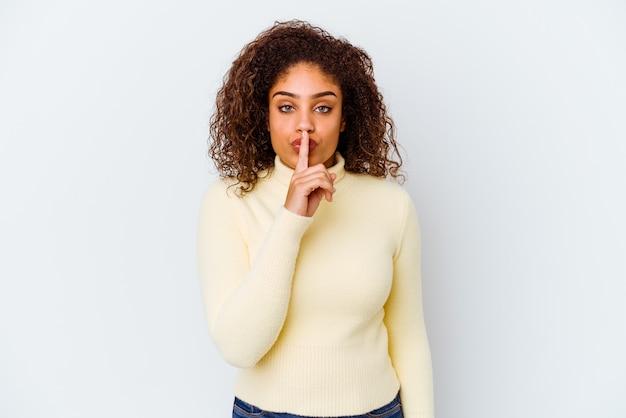 비밀을 유지하거나 침묵을 요구하는 흰 벽에 고립 된 젊은 아프리카 계 미국인 여자