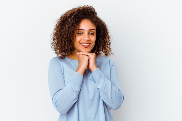 Молодая афро-американская женщина, изолированная на белой стене, держит руки под подбородком, счастливо смотрит в сторону.