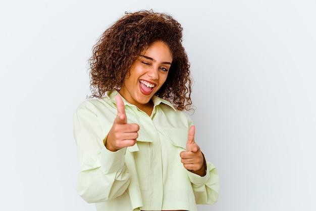 Молодая афро-американская женщина изолированная на белой стене указывая пальцами вперед.
