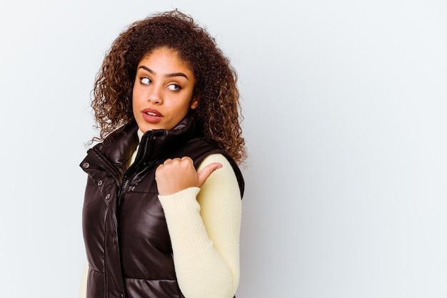 멀리 엄지 손가락으로 흰 벽 점에 고립 된 젊은 아프리카 계 미국인 여자, 웃음과 평온한