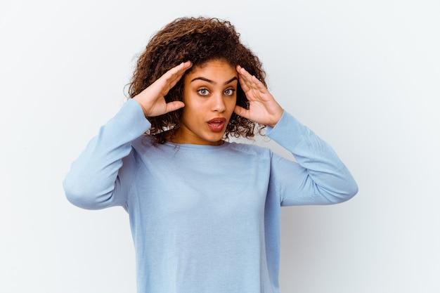 즐거운 놀라움을 받고, 흥분하고 손을 올리는 흰 벽에 고립 된 젊은 아프리카 계 미국인 여자.