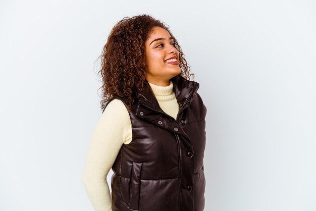 Молодая афро-американская женщина изолирована на белой стене расслабленным и счастливым смехом, вытянув шею, показывая зубы
