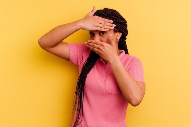 노란색 배경에 고립 된 젊은 아프리카 계 미국인 여자는 얼굴을 덮고 당황 손가락을 통해 카메라에 깜박입니다.