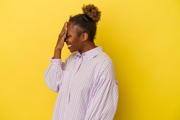 黄色の背景で隔離された若いアフリカ系アメリカ人の女性は、恥ずかしい顔を覆って、指を介してカメラで点滅します。