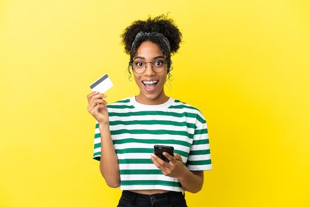 Молодая афро-американская женщина, изолированная на желтом фоне, покупает с помощью мобильного телефона и держит кредитную карту с удивленным выражением лица